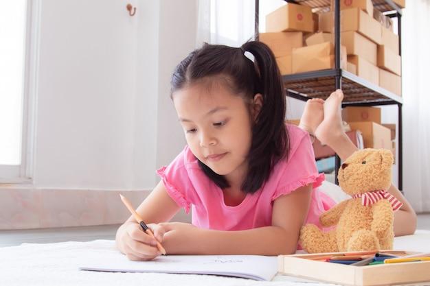 Crianças adoráveis elementares da escola em casa asiática deitam-se no chão, desenhando trabalhos de casa com lápis de cor, menina alegre feliz passou tempo concentrado desenho período de quarentena antes de voltar para a escola