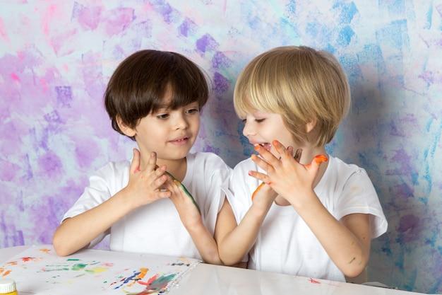 Crianças adoráveis em camisetas brancas, brincando com tintas multicoloridas
