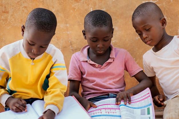 Crianças africanas em close lendo juntas