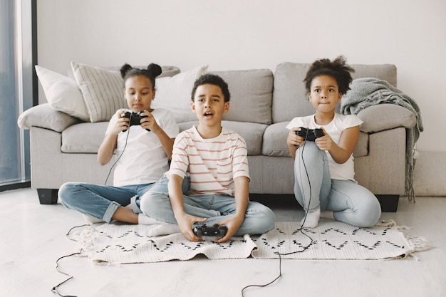 Crianças africanas jogando videogame. crianças com roupas leves. controlador nas mãos das crianças.