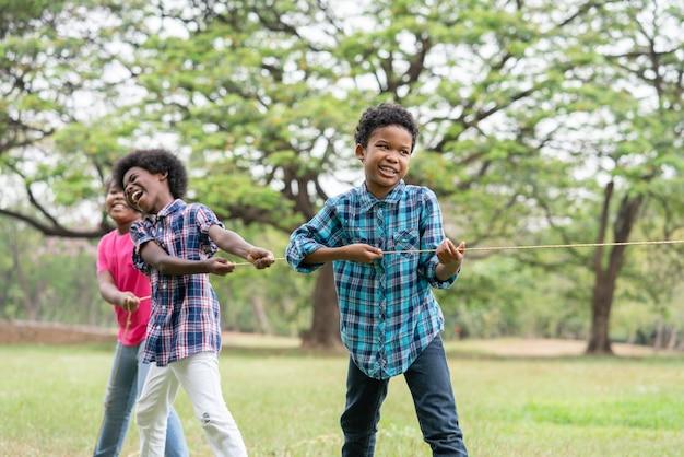 Crianças afro-americanas brincando de cabo de guerra à corda no parque