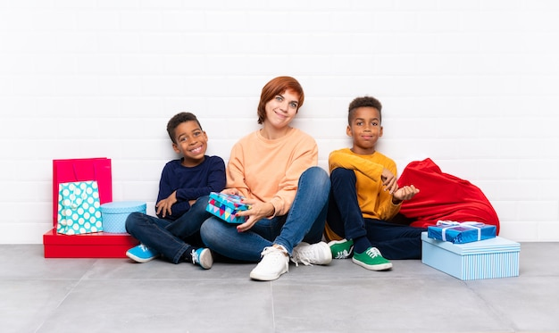 Crianças afro-americanas com sua mãe entre muitos presentes para as férias de natal