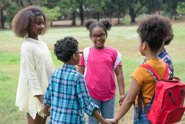Crianças afro-americanas em pé e de mãos dadas juntos em círculo no parque, conceito ao ar livre de educação