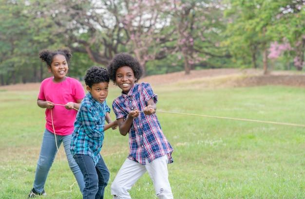 Crianças afro-americanas felizes brincando de cabo de guerra no parque conceito de educação ao ar livre