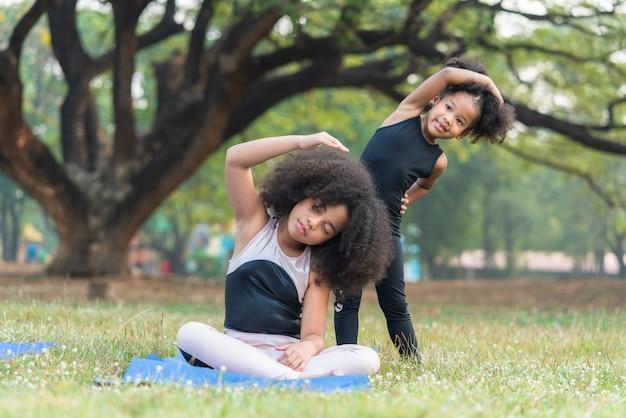 Crianças afro-americanas praticam ioga no parque ao ar livre