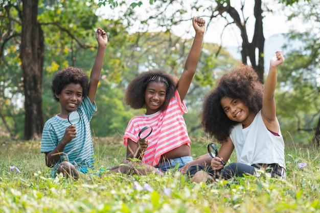 Crianças afro-americanas sentadas na grama olhando pela lupa