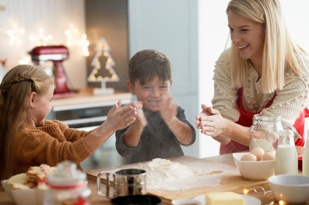 Crianças agarrando com farinha enquanto assam biscoitos
