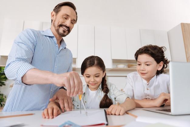 Crianças agradáveis e alegres sentadas no balcão da cozinha e aprendendo a usar uma bússola enquanto observam o pai escrevendo um círculo