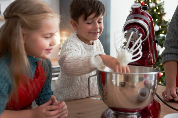 Crianças ajudando a mãe com bolos de natal