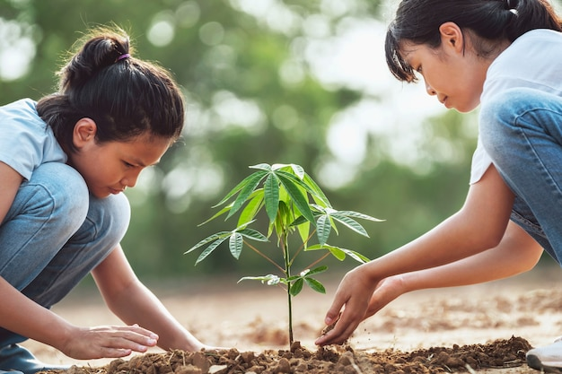 Crianças ajudando a plantar árvores no jardim para salvar o mundo. conceito de eco ambiente