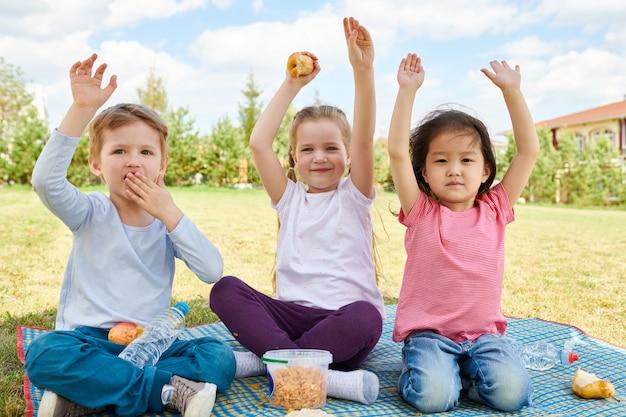 Crianças alegres, aproveitando o piquenique
