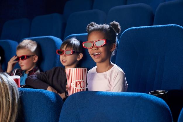 Crianças alegres, assistindo filme em óculos 3d, no cinema.