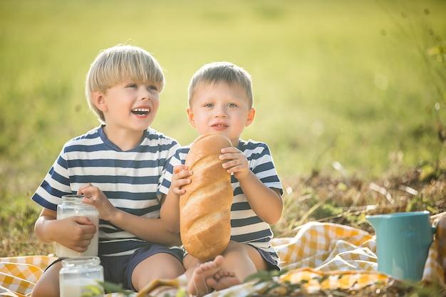 Crianças alegres, bebendo leite fresco ao ar livre