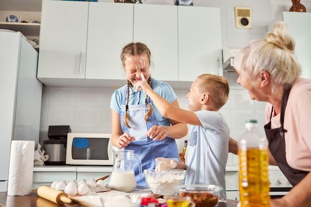 Crianças alegres borrando farinha no rosto umas das outras na cozinha