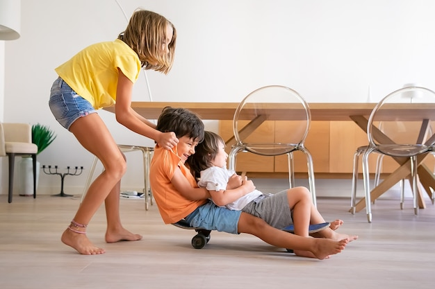 Crianças alegres brincando com o skate em casa. adorável menina loira empurrando seus dois irmãos brincalhões. crianças felizes andando a bordo e se divertindo. infância, atividade de jogo e conceito de fim de semana