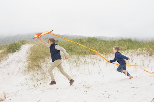 Crianças alegres correndo com pipa na praia