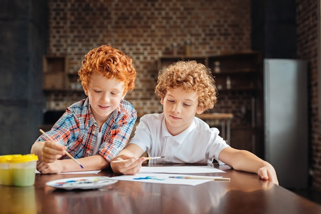Crianças alegres e concentradas, sentadas próximas umas das outras e focando sua atenção em pedaços de papel, enquanto são criativas e pintam algo interessante juntas.