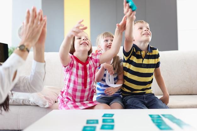 Crianças alegres e felizes jogando jogo de tabuleiro em casa