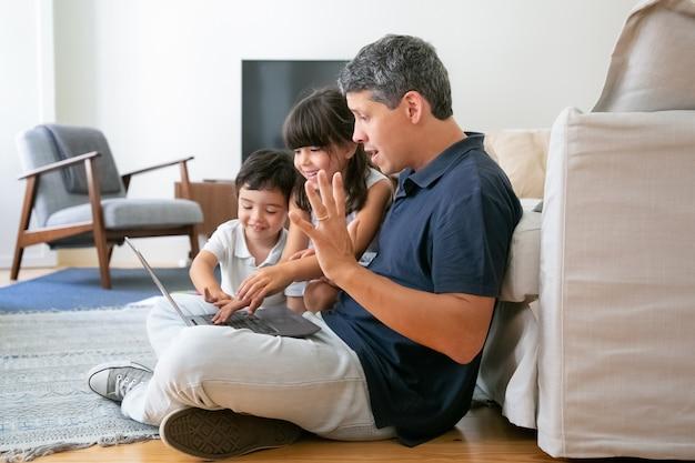 Crianças alegres e pai animado usando laptop juntos, sentados no chão do apartamento, navegando na internet.