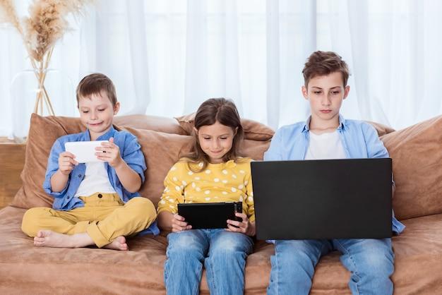 Crianças alegres em roupas casuais estão usando gadgets, olhando para a câmera e sorrindo enquanto estão sentadas juntas no sofá