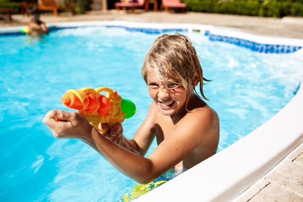 Crianças alegres jogando pistolas, regozijando-se, pulando, nadando na piscina.
