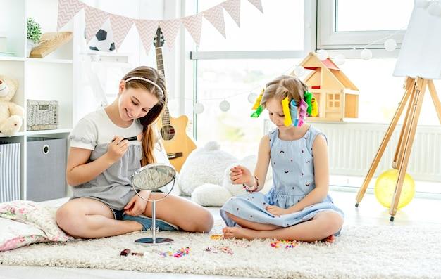 Crianças alegres meninas brincando com maquiagem