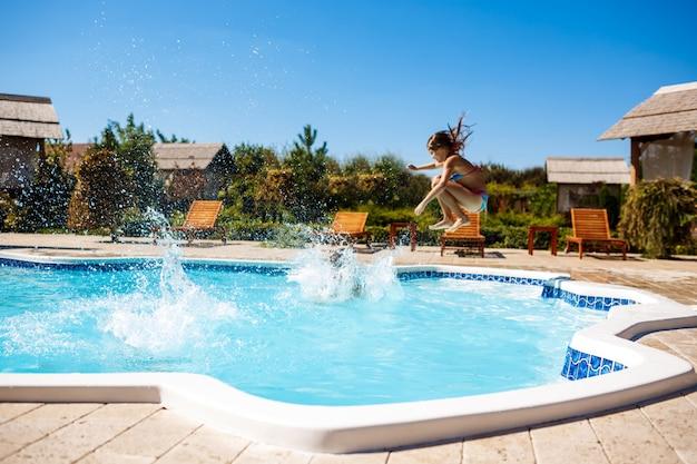 Crianças alegres, regozijando-se, pulando, nadando na piscina.