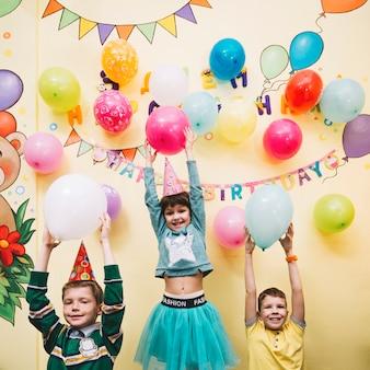 Crianças alegres segurando balões