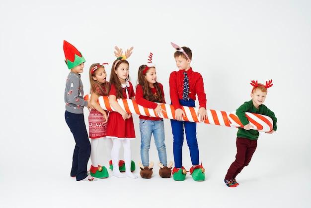 Crianças alegres segurando um enorme bastão de doces