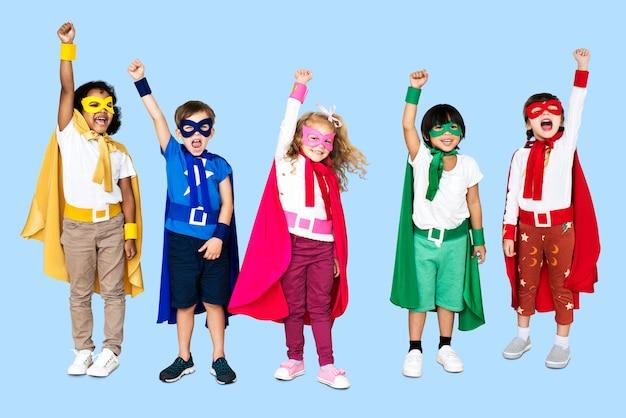 Crianças alegres, vestindo trajes de super-heróis