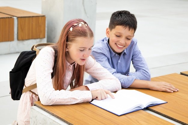 Crianças, alunos, adolescentes lêem no pátio da escola no banco de madeira. menino e menina são apaixonados por livro, conceito de leitura