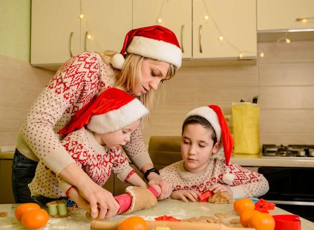 Crianças americanas estão preparando a massa, assando biscoitos de gengibre na cozinha no dia de inverno.
