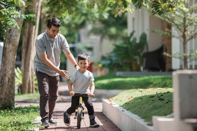 Crianças andam de bicicleta por seu pai