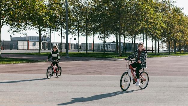 Crianças andando de bicicleta juntas lá fora