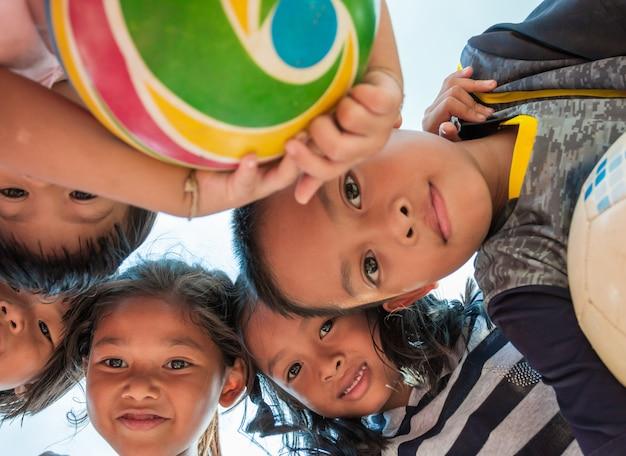 Crianças animadas ficar em círculo, abraçando a olhar para a câmera jogando juntos
