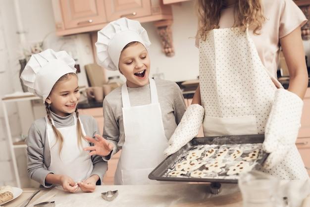 Crianças animadas olhem para a mãe segura uma panela com cookies.