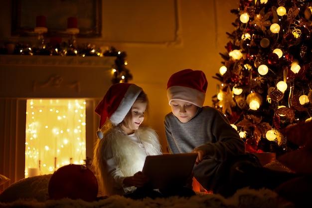Crianças animadas perto de árvore de natal