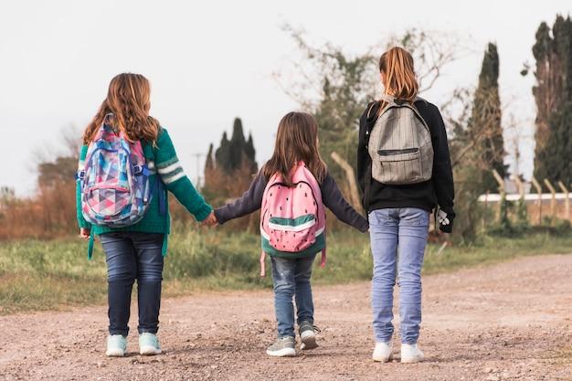 Crianças anônimas caminhando para a escola