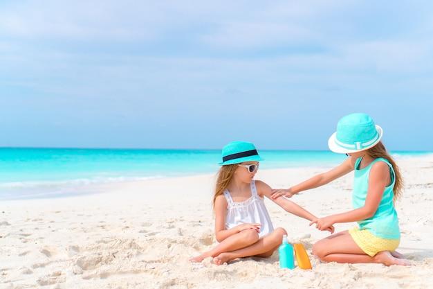 Crianças, aplicar protetor solar uns aos outros na praia. o conceito de proteção contra radiação ultravioleta