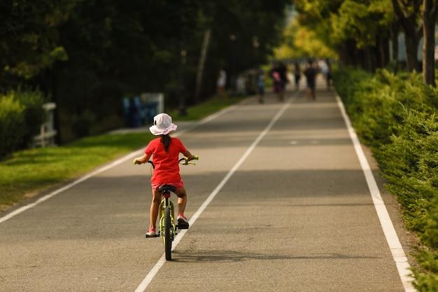 Crianças aprendendo a dirigir uma bicicleta em uma calçada do lado de fora.