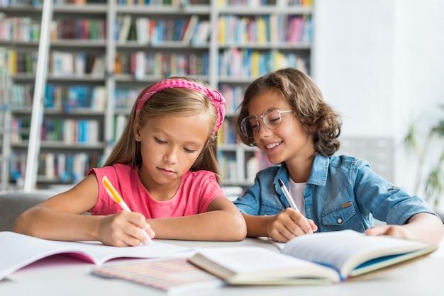 Crianças aprendendo e fazendo seus deveres de casa na biblioteca