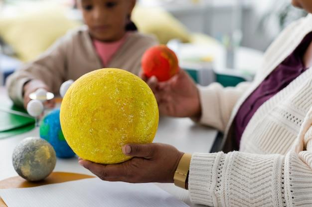 Crianças aprendendo sobre planetas na sala de aula