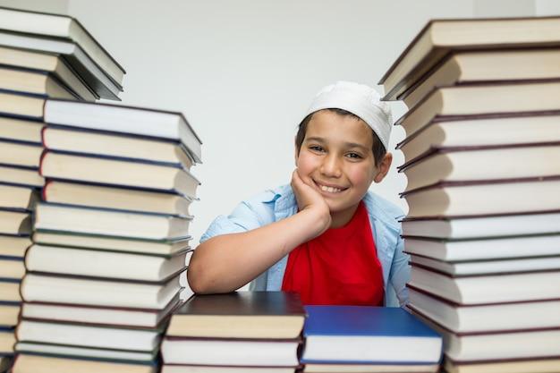 Crianças árabes muçulmanas com muitos livros na biblioteca