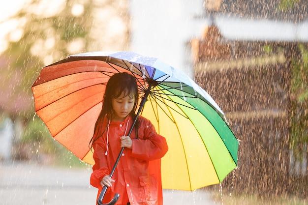 Crianças asiáticas abrindo guarda-chuvas brincando na chuva, ela está vestindo uma capa de chuva.