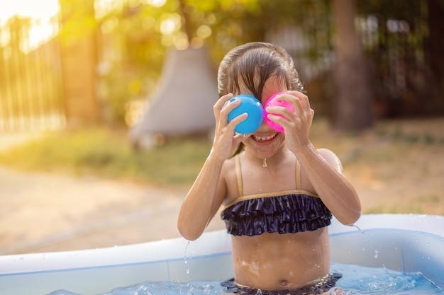 Crianças asiáticas brincando no verão em uma pequena piscina