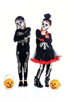 Crianças asiáticas com cara de pintura e trajes de halloween