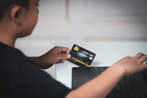 Crianças asiáticas de yong com a pele amarela, prendendo o cartão de crédito preto, portátil preto na tabela branca.