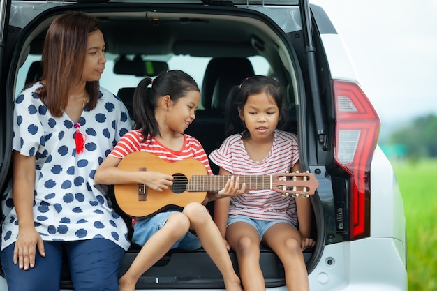 Crianças asiáticas e sua mãe tocando violão e cantando uma música juntas no porta-malas de um carro