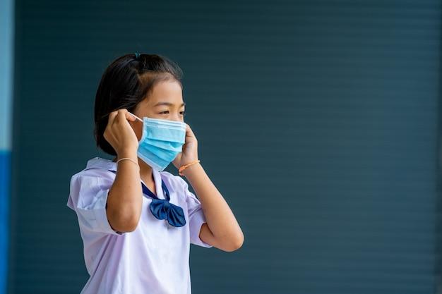 Crianças asiáticas em uniforme escolar usando máscara protetora para proteção contra covid-19, de volta às aulas para um novo conceito de estilo de vida normal.