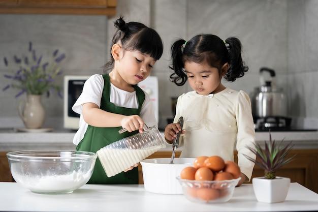 Crianças asiáticas gostam de cozinhar pães na cozinha
